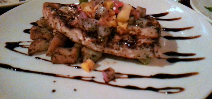 Grilled swordfish entrée topped with a dragon fruit and mango salsa and served with potatoes and asparagus.